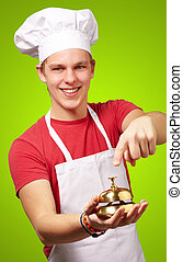 portrait of young cook man pressing a golden bell over green...