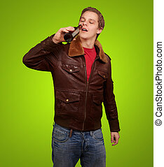 portrait of young man drinking beer against a green...
