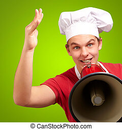 portrait of happy cook man shouting using megaphone over green background