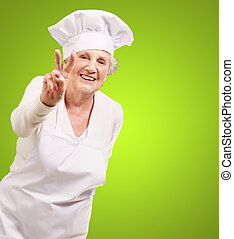 portrait of cook senior woman doing approval gesture over green background
