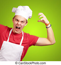 portrait of young cook man wearing apron doing aggressive gesture over green
