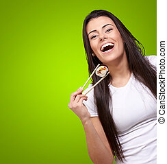 portrait of young woman holding sushi against a green...