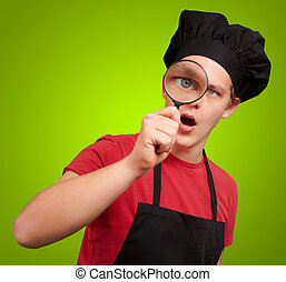 portrait of young cook man looking through a magnifying...