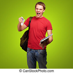 young angry student man roughing a sheet over green...