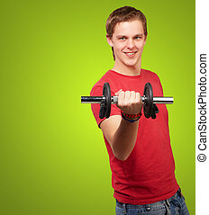 portrait of young man with weights over green background