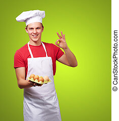 portrait of young cook man holding egg box and doing good gesture over green
