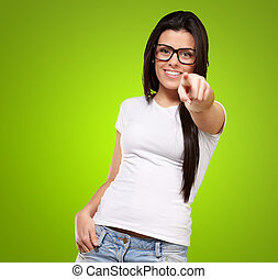 portrait of young woman pointing with finger against a green background
