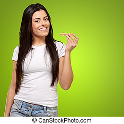 portrait of young woman eating cereal bar over green...