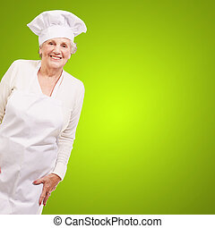 portrait of cook senior woman smiling over green background