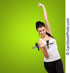portrait of young woman doing fitness with weights over green background