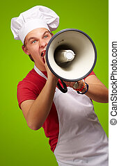 portrait of young cook man screaming with megaphone over green background