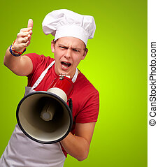 portrait of young cook man screaming with megaphone and gesturing over green background