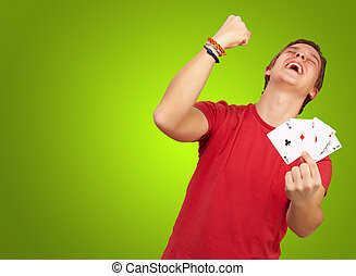 portrait of young man doing a winner gesture playing poker over green