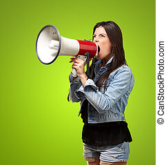 portrait of young woman screaming with megaphone against a green background