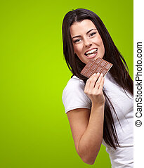 portrait of young woman eating chocolate bar against a green background
