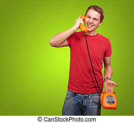portrait of young man talking with vintage telephone over green background