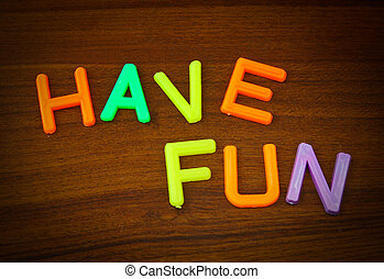 Have fun in colorful toy letters on wood background