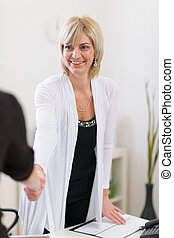 Smiling senior business woman shaking visitors hand