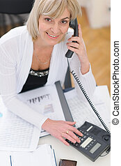 Smiling middle age business woman making phone call