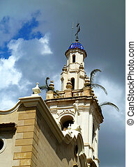 palm sunday - church spire with palm fronds against cloudy...