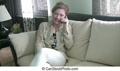 Woman sitting on sofa talking on phone