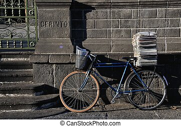 Postman Bike with a bunch of papers leaned against the wall...