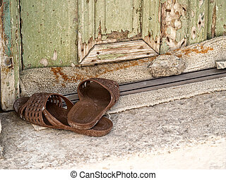 Plastic slippers at the doorstep - A pair of old plastic...