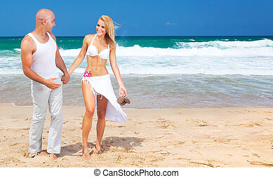 Happy couple walking on the beach, young new family spends...