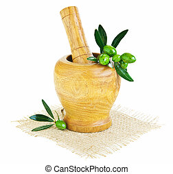 Wooden mortar with fresh green olives, preparing medicine...