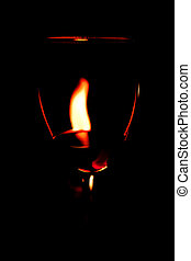 Red wine glass and flame - flame from candle seen through...