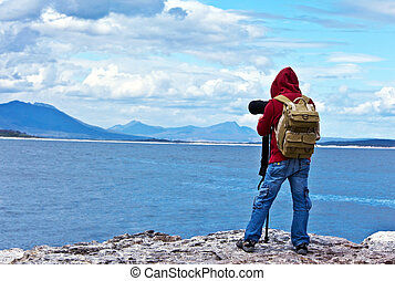 Wildlife photographer traveler enjoying ocean view from top...
