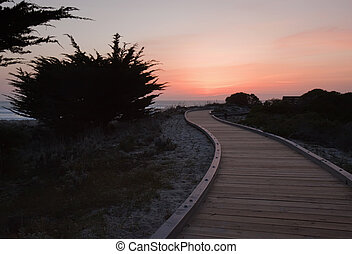 Sunset over a walkway through sand dunes at Asilomar State...