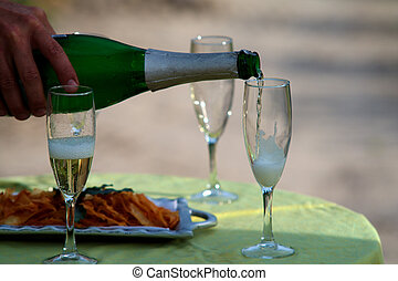 Champagne flutes - A row of Champagne flutes are being...