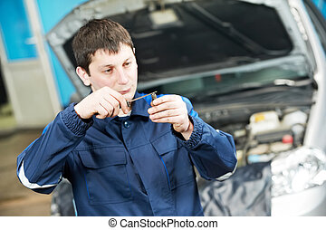 car mechanic inspecting engine sparking plug - car mechanic...