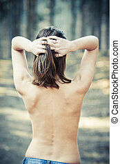 Back of a topless woman with jeans,  looking at the forest