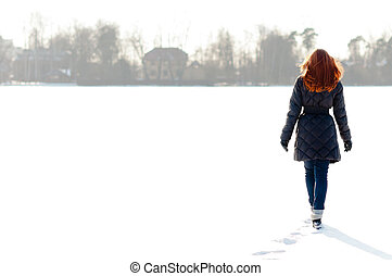 Pretty girl walking on frozen lake - Pretty red haired girl...