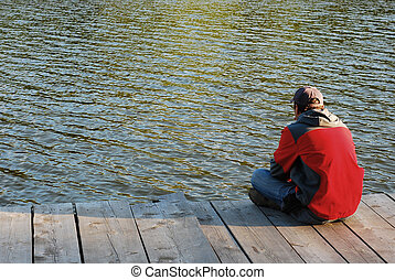loneliness - man standing alone on the dock