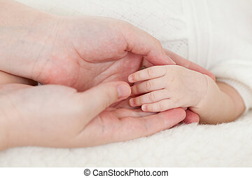 parents hand holding babys hand