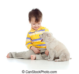 smiling child playing with a puppy - adorable boy playing...