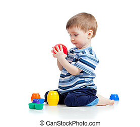 Cute little child is playing with toys while sitting on...