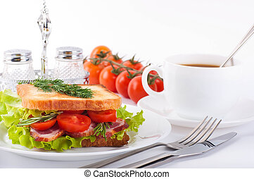Sandwich from smoked meat and tomatoes, a cup of coffee