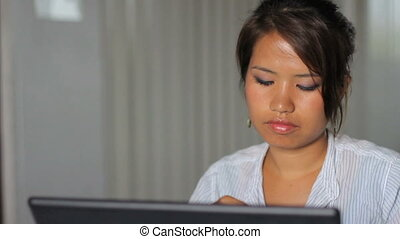 Asian Girl Listens To Music At Work - A pretty Asian girl...