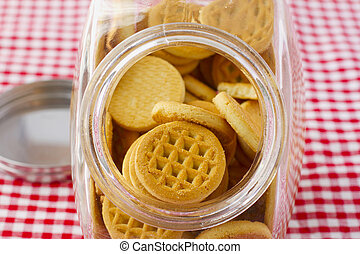 Biscuits - Round biscuits in a glass vase over a white and...