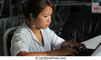 Asian Office Worker On Lap Top - A pretty Asian girl does...