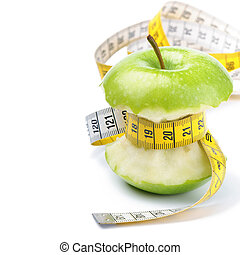 Green apple core and measuring tape Diet concept