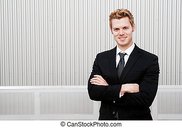 Portrait of a happy young businessman in suit standing...