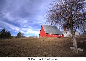 Big barn by field.