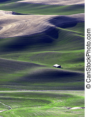 Building dwarfed by the Palouse. - A building appears to be...