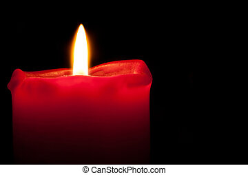 Red Candle burning with an orange flame in darkness