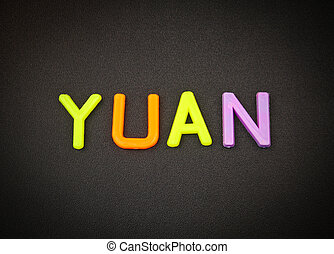 Yuan in colorful toy letters on black background